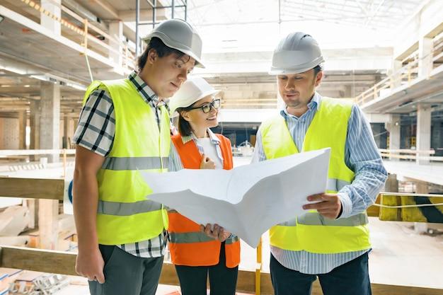 Grupo de engenheiros, construtores, arquitetos no canteiro de obras, procurando na planta