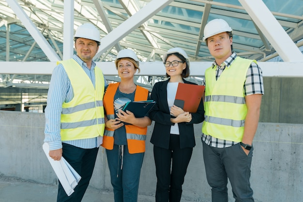 Grupo de engenheiros, construtores, arquitetos no canteiro de obras.