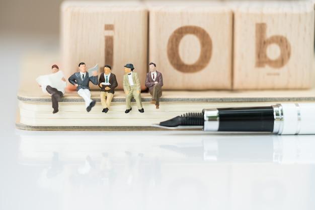Grupo de equipe do negócio que senta-se no caderno com palavra da pena e do trabalho dos blocos de madeira.