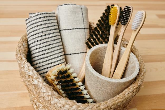 Grupo de escovas de dente, toalhas enroladas e duas escovas em uma pequena cesta de pé no chão de madeira