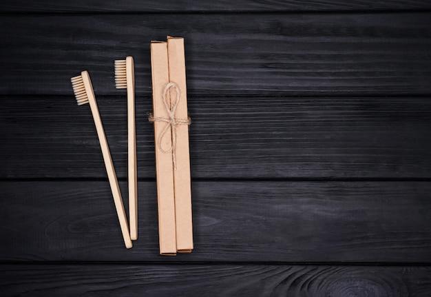 Grupo de escovas de dentes de bambu ecológicas em fundo preto de madeira