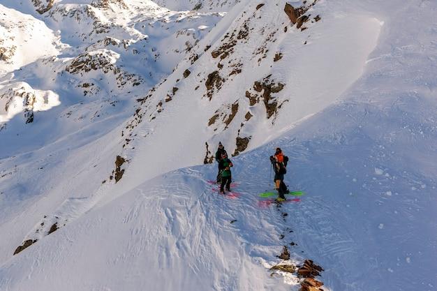 Grupo de esquiadores fora de pista se preparando para iniciar um passeio nas montanhas de ischgl, na áustria. dia ensolarado. topo da montanha.