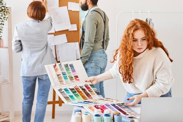 Grupo de estilistas trabalhando em um ateliê com quadro de ideias e paleta de cores