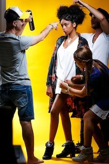 Grupo de estilistas trabalhando na imagem de um jovem modelo em uma parede amarela