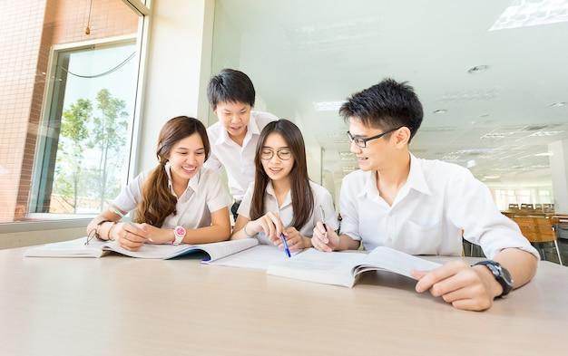 Grupo de estudante asiática feliz em estudo em sala de aula