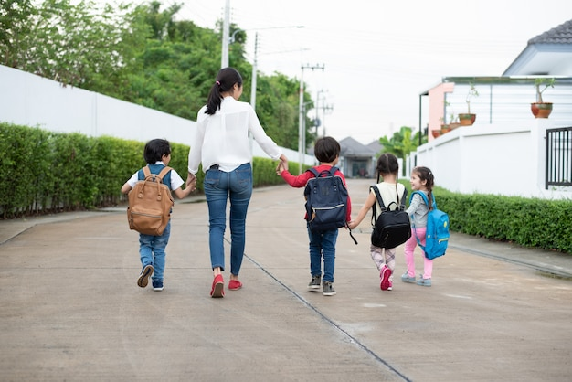 Grupo de estudante pré-escolar e professor de mãos dadas e caminhando para casa.