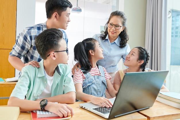 Grupo de estudantes adolescentes asiáticos e seu professor de ciência da computação reunidos na mesa com um laptop para discutir o programa de computador