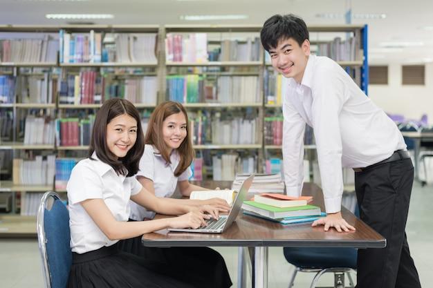 Grupo de estudantes asiáticos em uniforme estudando juntos na biblioteca.