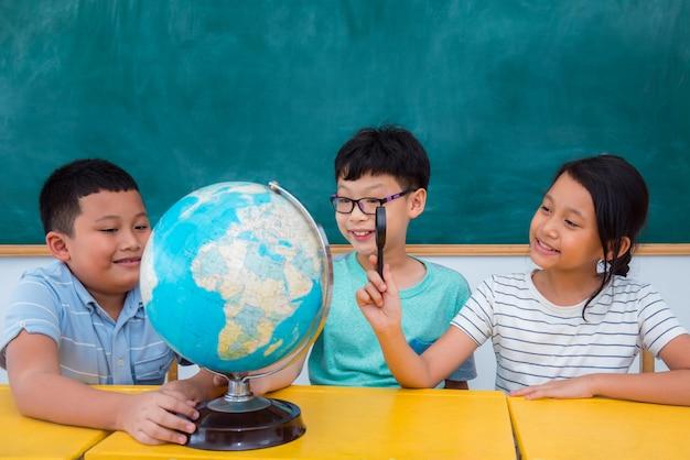 Grupo de estudantes asiáticos estudando geografia em sala de aula