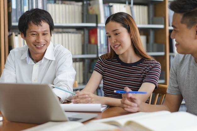 Grupo de estudantes asiáticos pesquisando para projeto na biblioteca da universidade.