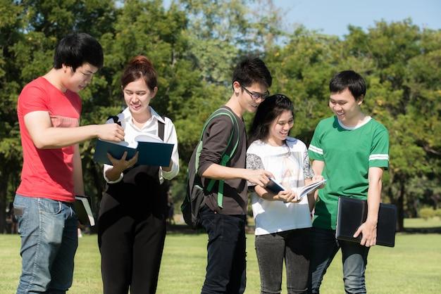 Grupo de estudantes asiáticos vestido casual em pé no parque ao ar livre