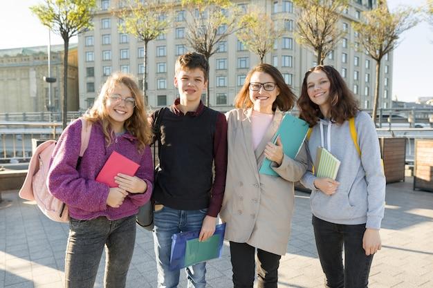 Grupo de estudantes com professor, adolescentes conversando com uma professora