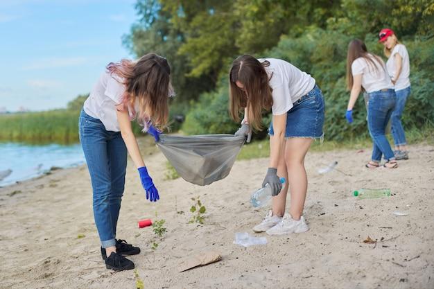 Grupo de estudantes com professor na natureza, fazendo a limpeza do lixo plástico
