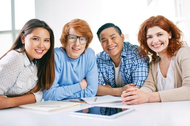 Grupo de estudantes de sorriso que sentam-se na sala de aula