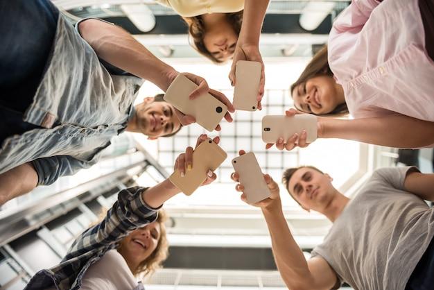 Grupo de estudantes em pé em círculo e usando telefones.