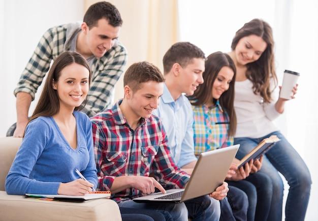 Grupo de estudantes estão sentados no sofá.