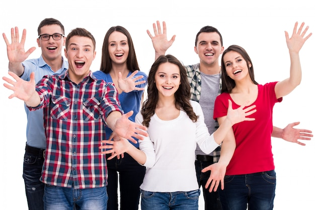 Grupo de estudantes felizes a sorrir estão de pé juntos.