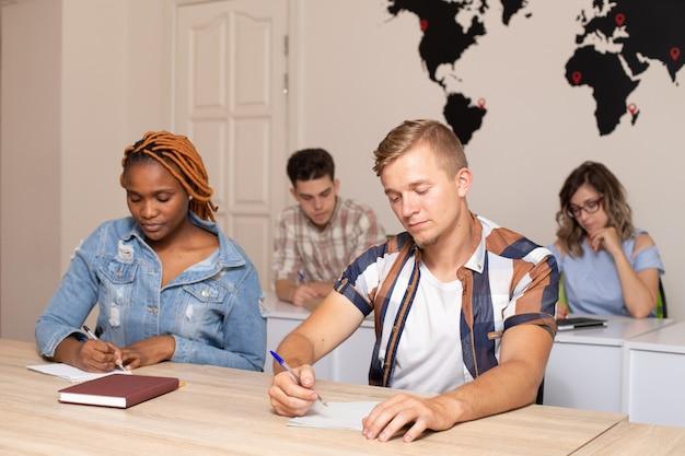 Grupo de estudantes internacionais em sala de aula com o mapa do mundo na parede