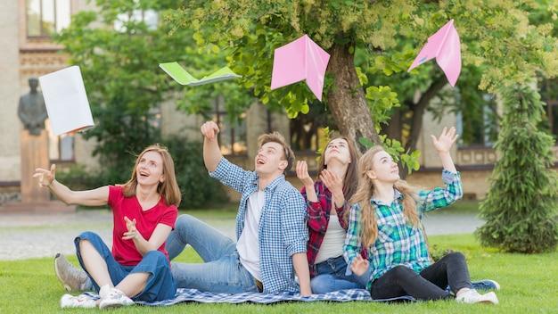Grupo de estudantes jogando livros no ar