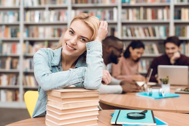 Grupo de estudantes multiculturais étnicos na biblioteca. menina branca com livros.