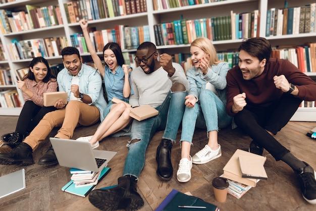 Grupo de estudantes multiculturais étnicos na biblioteca