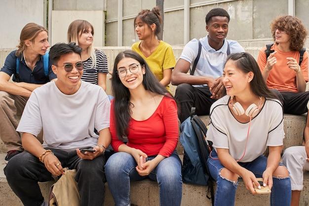 Grupo de estudantes multiétnicos alegremente olhando para a câmera durante um intervalo