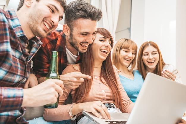 Grupo de estudantes ou adolescentes com computadores laptop e tablet pc em casa se divertindo