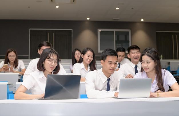 Grupo de estudantes que trabalham com laptop em sala de aula
