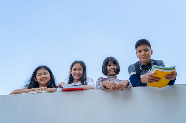 Grupo de estudantes rir feliz em pé juntos sobre a parede passarela balckground céu bule