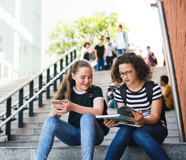 Grupo de estudantes sentados na escada usando lptop