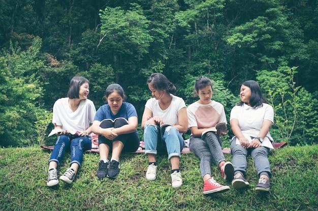 Grupo de estudantes sentados na grama