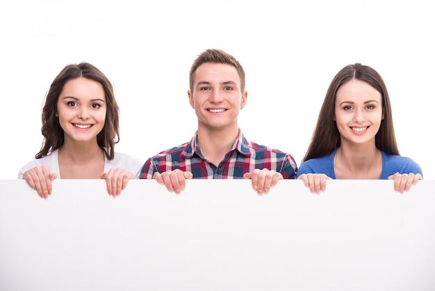 Grupo de estudantes sorridentes com placa em branco