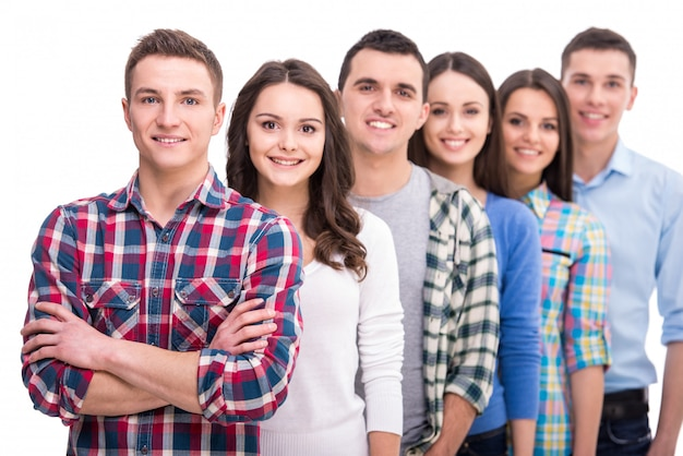 Grupo de estudantes sorridentes está de pé.