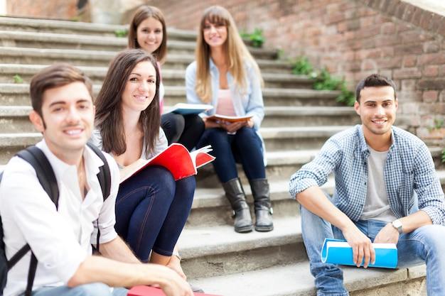 Grupo de estudantes sorridentes, sentado em uma escada