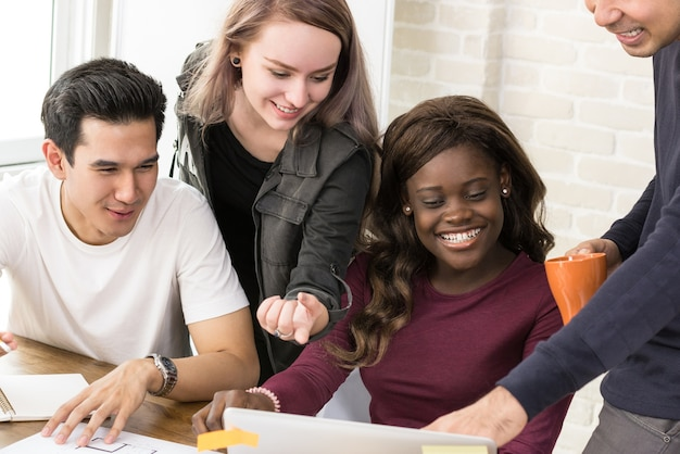 Grupo de estudantes universitários de raça mista trabalhando juntos