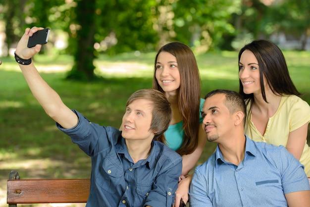 Grupo de estudantes universitários jovens felizes fazendo selfie.