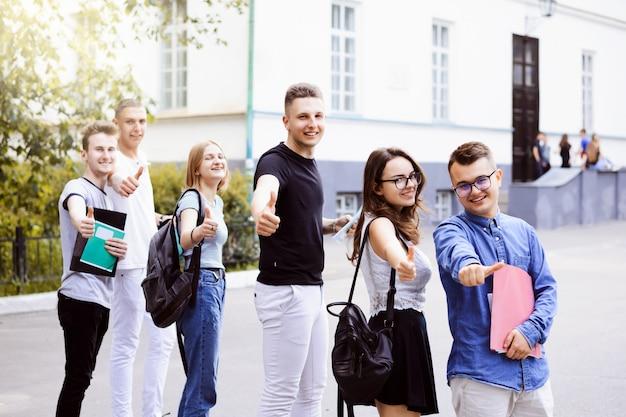 Grupo de estudantes universitários, mostrando os polegares