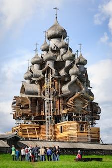 Grupo de excurtion, olhando para a igreja de madeira em kizhi sob reconstrução