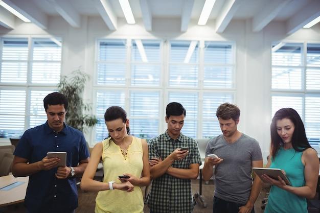 Grupo de executivos de negócios que usa a tabuleta digital e pho móvel