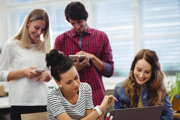 Grupo de executivos de negócios usa a tabuleta digital, laptop e mo