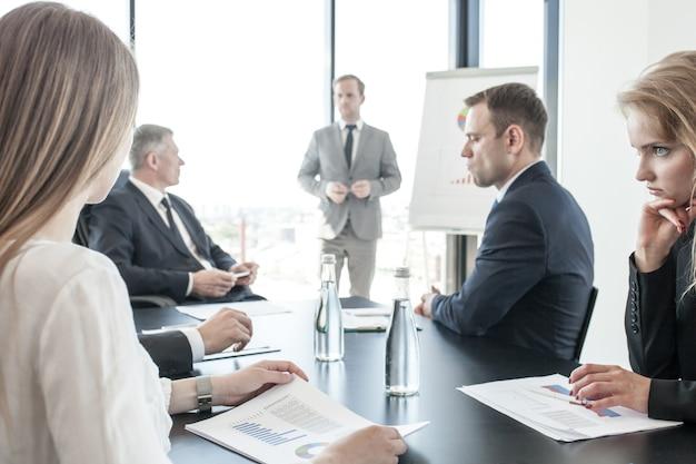 Grupo de executivos em reunião assistindo a apresentação de relatórios em diagramas e gráficos em flip chart no escritório