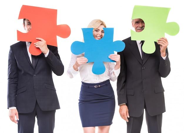 Grupo de executivos que montam o enigma de serra de vaivém.