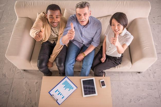 Grupo de executivos que mostram os polegares acima no escritório.