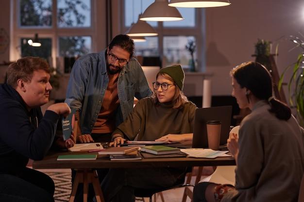Grupo de executivos sentados à mesa e planejando trabalhar juntos em equipe no escritório