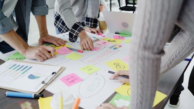 Grupo de executivos vestidos ocasionalmente que discutem ideias no escritório.