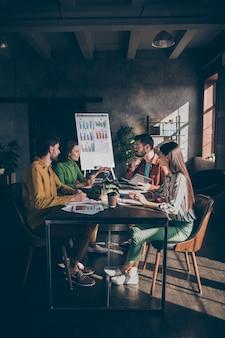 Grupo de experiência, alunos reunidos em uma grande estação de trabalho escura, sentar na mesa