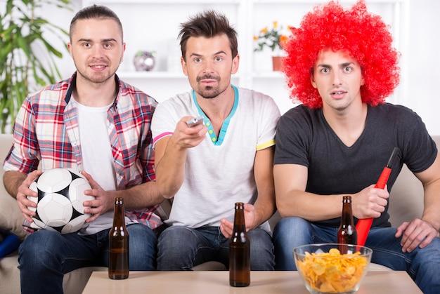 Grupo de fãs de esportes estão assistindo jogo na tv em casa.