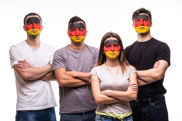 Grupo de fãs de torcedores de pessoas das seleções da alemanha com a cara da bandeira pintada isolada no branco. emoções dos fãs.