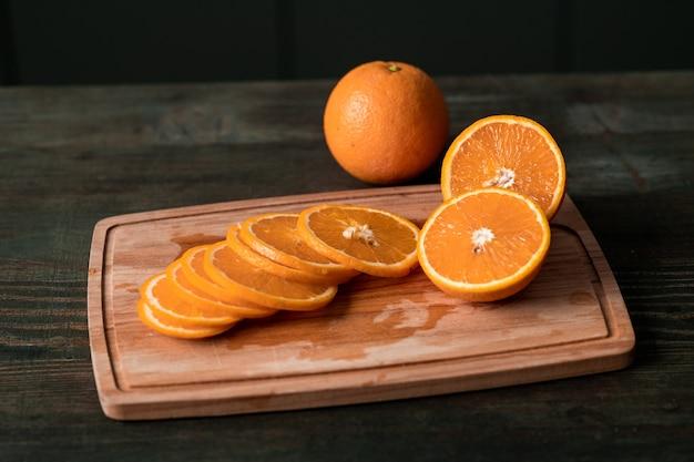 Grupo de fatias de laranja frescas e metades das frutas em uma tábua de madeira na mesa da cozinha cortadas pela dona de casa para comer