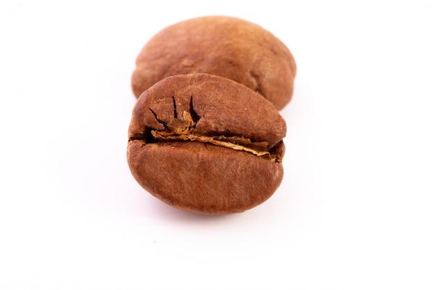 Grupo de feijões de café roasted isolados, fim acima.
